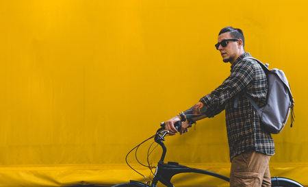 Handsome Adult Man In Sunglasses Walks With A Bicycle Along A Yellow Wall Copy Space