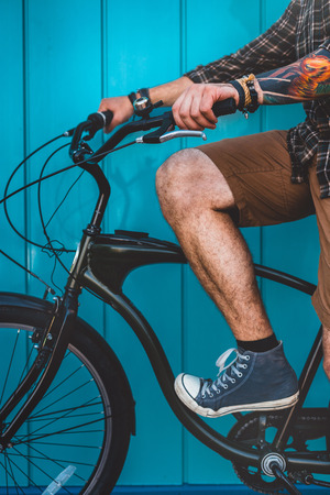 Unrecognizable Adult Man Sitting On A Bicycle Along A Blue Wall Background Daily Lifestyle Urban Resting Concept Stok Fotoğraf - 82331703