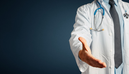 Unrecognizable Man Doctor Holds Out His Hand To Say Hello. Greeting Patient. Healthcare Medicine Concept