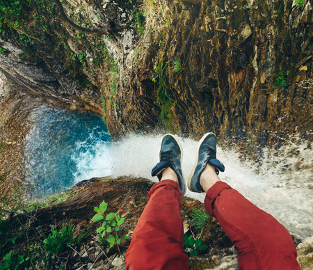 Männlicher Reisender, der auf Klippe mit Wasserfallansicht sitzt. Reise-Lebensstil-Abenteuerurlaubkonzept Standard-Bild - 82607078