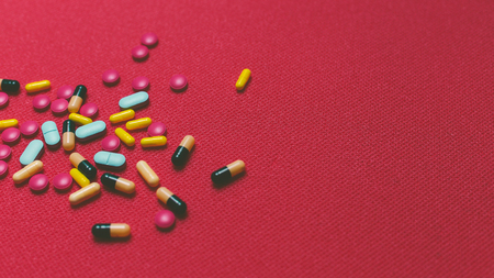 sobredosis: Different Colorful Pills, Tablets And Capsules On Red Background
