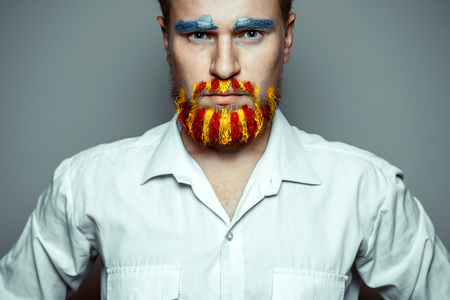 Portrait Of A Stern Man With A beard, Unraveled In Colors Of The Flag Of Catalonia. Referendum For The Separation Of Catalonia From Spain. Democracy Independence Concept