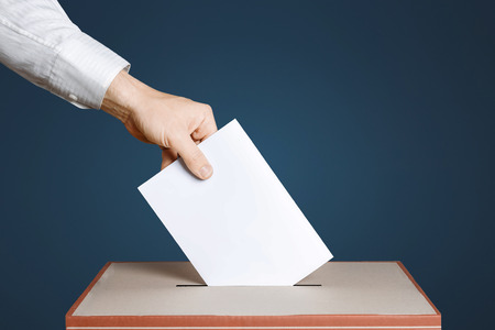 politic: Voter Holds Envelope In Hand Above Vote Ballot. Blue background. Democracy Concept Stock Photo