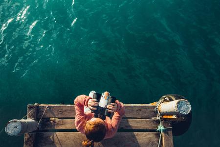 Jong meisje zit op de pier en kijkt op zee door middel van een verrekijker, bovenaanzicht. Adventure Vacation Discovery Travel Concept