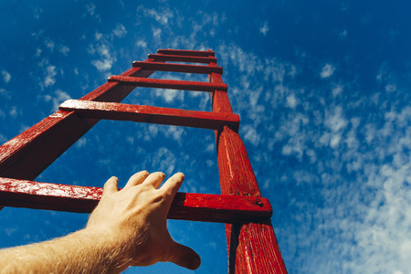 Hand Of Man Reaching For Red Ladder Leading To A Blue Sky. Development motivation Career Growth Concept Stock Photo - 88574857