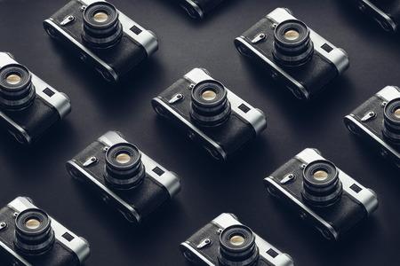 黒の背景面上のヴィンテージフィルムカメラ。創造性レトロな技術コンセプト