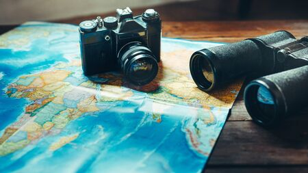 Accessories for travel  Vintage Film Camera, Map And Binoculars On Wooden Table, Front View. Adventure Travel Scout Journey Concept