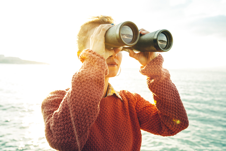 Beautiful Young Girl Looking Through Binoculars At The Sea On A Bright Sunny Day. Wanderlust Journey Concept Banco de Imagens