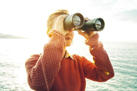 Belle jeune fille regardant à travers les jumelles à la mer sur une journée ensoleillée lumineuse. Wanderlust Journey Concept Banque d'images