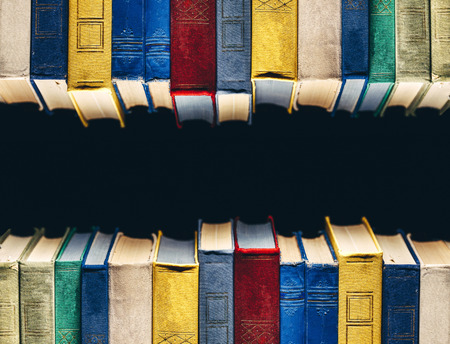 Old Books In A Row In Library On Black Background With Copy-Space Stock Photo