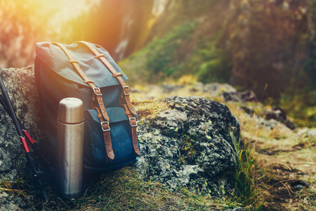 Hipster Blue Backpack, Thermos And Trekking Poles Closeup, Front View. Tourist Traveler Bag On Rocks Background. Adventure Hiking Journey Concept 版權商用圖片