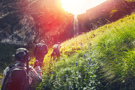 Group Of Hikers Tourists Walking Uphill To Waterfall. Travel Adventure Outdoor Concept Stock Photo