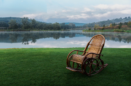 Rocking Chair On Green Grass Against Lake. Recreation Relaxation Concept