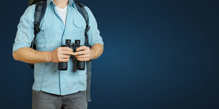 Young Traveler Man With Backpack And Binoculars Seeking Direction On Blue Background. Hiking Tourism Journey Concept