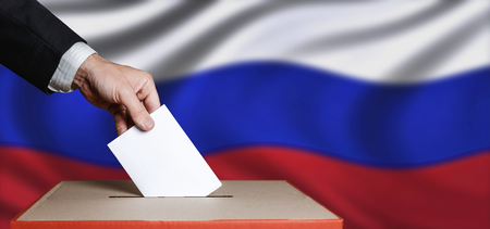Voter Holdings Envelope In Hand Above Vote Ballot On Russia Flag Background. Freedom Democracy Concept