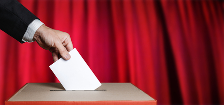 Voter Holds Envelope In Hand Above Vote Ballot On Red Background. Freedom Democracy Concept