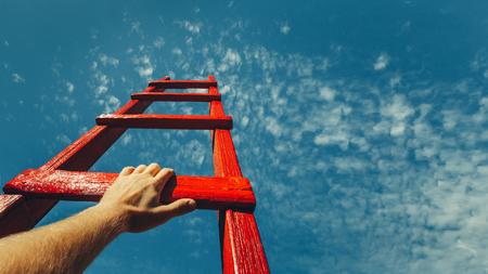 Desarrollo Logro Motivación Carrera Crecimiento Concepto. Mans mano alcanzando la escalera roja que conduce a un cielo azul Foto de archivo