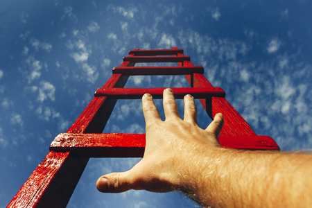 Development Motivation Career Growth Concept. Mans Hand Reaching For Red Ladder Leading To A Blue Sky Stock Photo