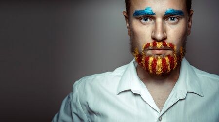 Portrait Of A Stern Man With A beard, Unraveled In Colors Of The Flag Of Catalonia. Creativity Portrait Concept
