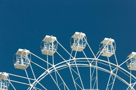 Ferris wheel against the blue sky. Summer Season Holiday Entertainment Concept