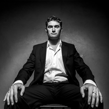 Handsome man in a business suit sitting on a chair, black and white portrait, low angle shot Stock Photo
