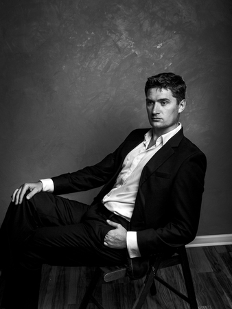 Handsome man in a business suit sits on a chair and looks away, style fashion black and white portrait Stock Photo
