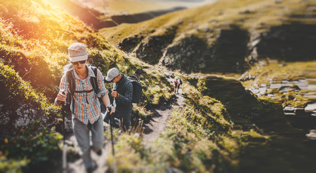 Group Of Hikers Walking Along In The Summer Mountains, Journey Travel Trekking Concept