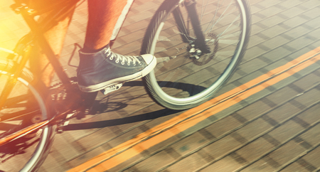 Unrecognizable Cyclist In Sneakers Rides Bicycle Path In Motion Blur Summer Day. Point of view shot