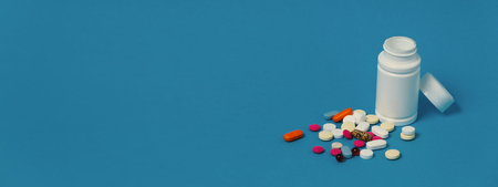 Global Medicine Healthcare Pharmacy Concept. Multicolored Pills And White Bottle On Blue Surface. 写真素材