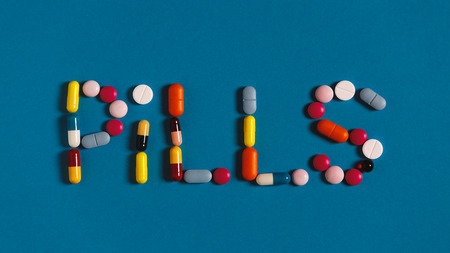 Word Pills Is Lined With Colored Pills And Tablets On A Blue Background, Top View 写真素材