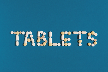 Global Medicine And Health Care Pharmacy Concept. Word Tablets Is Lined With White Pills On A Blue Background, Top View