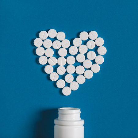 Global Medicine And Health Care Pharmacy Concept. Sign Heart From White Tablets Medicament On Blue Background, Topv View 写真素材
