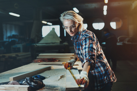 Beautiful woman carpenter designer works with ruler, make notches on the tree in workshop.  Image of modern femininity. Concept of professionally motivated women 写真素材 - 117181326