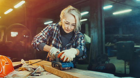 White middle aged woman selects wood in workshop. Concept of professionally oriented motivated modern woman. Gender equality, image of femininity