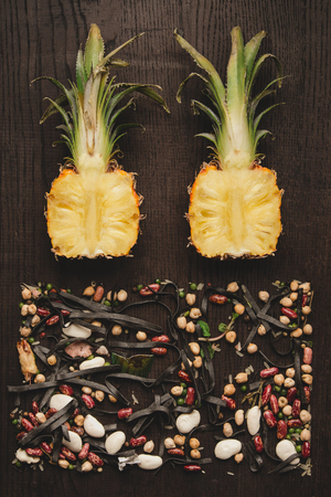 Food design minimalism flat lay. Cut along the pineapple and evenly spread out the beans, top view 写真素材 - 117181352
