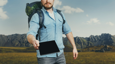Unrecognizable man traveler with backpack holds a digital tablet. The concept of information assistance in travel and tourism 写真素材