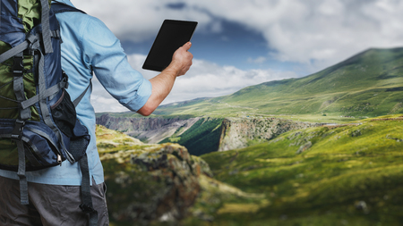 Young traveler hiker with backpack looking at the route map in a digital tablet. The concept of a modern adventure
