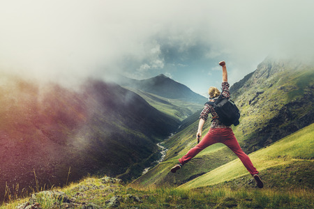 Young man traveler jumps on a background of mountain and enjoys view of summer mountains, rear view with copy-space. Concept of achieving motivation wanderlust 写真素材