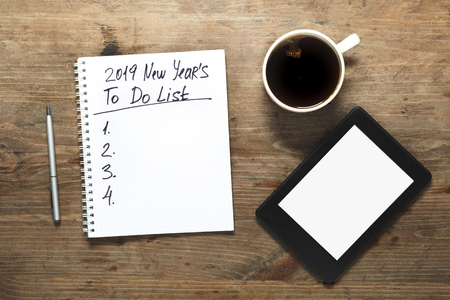 2019 New year Motivation Concept. Number and text on notepad. Tablet, pen and cup of copy background, top view, flat lay