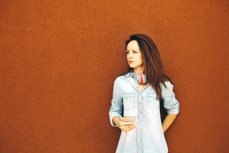 Beautiful modern young girl in headphones with a phone stands near the orange wall. The concept of urban style, youth and trends, feminism, emancipation, womens rights