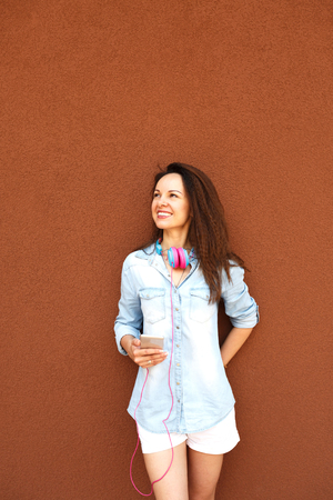 Happy fashionable girl with headphones and a telephone near the wall, smiling and enjoying. Concept of urban style, youth and trends, feminism, emancipation, womens rights 写真素材