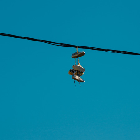 Sneakers hanging on a sky background. The concept of urban kultruta, sale of prohibited substances, ghetto 写真素材