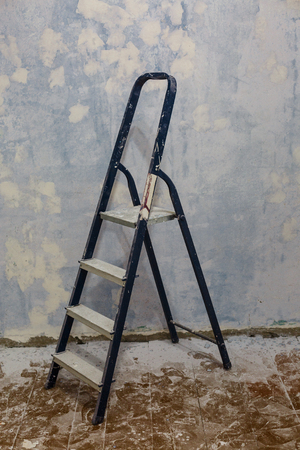 Foldable aluminum ladder on the background of the wall. Repair in home concept