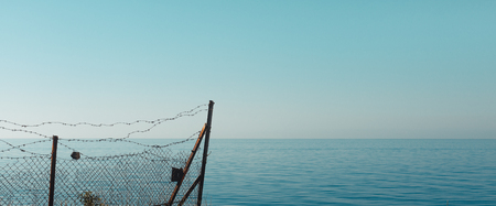 Fence and barbed wire against the background of the sea, sky and horizon. The concept of freedom, independence and contemplation