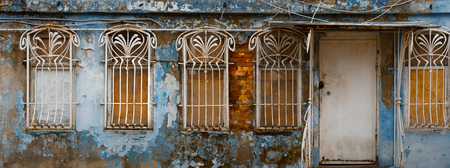 Appearance of the facade of an abandoned building with decorative bars on the windows, unrecognizable structure 写真素材