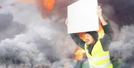 Protests yellow vests. A young man is holding a poster. The concept of revolution and protest, the struggle for equal rights, the electoral movement