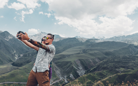 Couple of hikers do selfie on a camera against the backdrop of a picturesque summer mountain landscape. Travel adventure concept