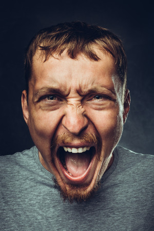 Creative male portrait. Young handsome man is screaming. Radical expression and emotion concept