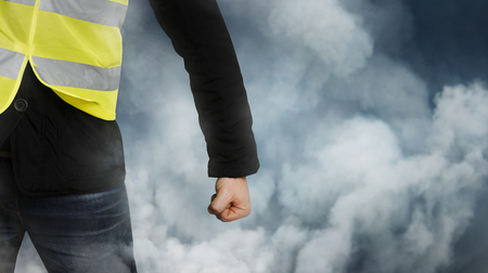 Yellow vests protests. An unrecognizable man clenched his fist in protest. The concept of revolution and protest on the blue background
