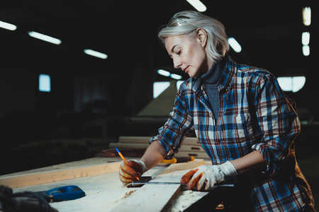 Beautiful middle aged woman carpenter designer works with ruler, make notches on the tree in workshop.  Image of modern femininity. Concept of professionally motivated women 写真素材